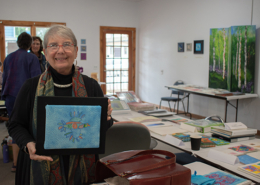 Artist-in-residence Marilyn Olsen showing one of her hand embroidered birds