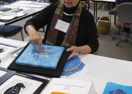 Artist-in-residence Marilyn Olsen discusses her hand embroidered birds with attendees